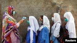 سکول کی عمارت میں داخل ہونے سے قبل طالبات کا ٹمپریچر چیک کیا جا رہا ہے