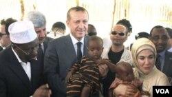 Presiden Somalia, Sharif Sheik Ahmed (kiri) mendampingi PM Turki Recep Tayyib Erdogan dan isterinya Emine Erdogan saat mengunjungi korban kelaparan di Mogadishu (19/8).