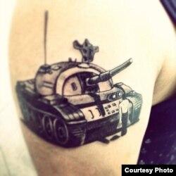 """两年前,巴丢草将""""坦克人""""的形象刺在他的右臂上,希望能不忘作画初心。(巴丢草提供)"""
