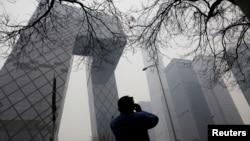 一名男子用手机拍摄北京的中国央视大楼。(2021年3月5日)