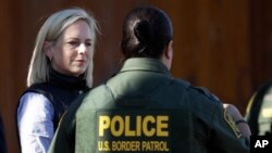 FILE - U.S. Department of Homeland Security Secretary Kirstjen Nielsen, left, speaks with Border Patrol agents near a newly fortified border wall structure, Oct. 26, 2018, in Calexico, Calif.