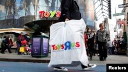 Warga membawa kantong plastik belanja dari toko Toys R Us di Times Square, New York City.