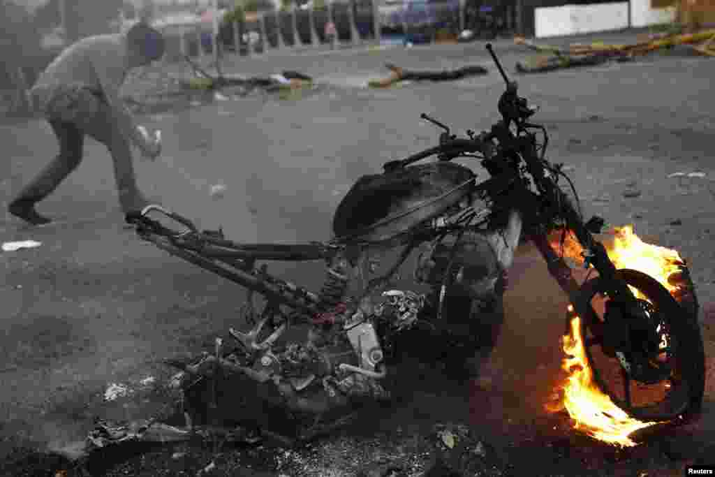 An anti-government demonstrator walks behind a burning motorcycle during a protest in San Cristobal, Venezuela, Feb. 27, 2014.