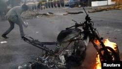 Một người biểu tình chống chính phủ đi qua một chiếc xe máy bị đốt sau một cuộc biểu tình ở San Cristobal,Venezuela, 27/2/2014.