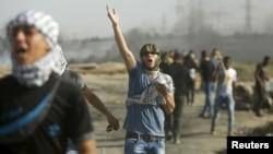 Para demonstran Palestina bereaksi terhadap gas airmata yang ditembakkan tentara Israel (16/10). Kekerasan terbaru ini telah menewaskan puluhan orang.