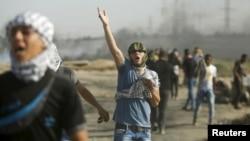 2015年10月16日,一名巴勒斯坦抗議者在加沙城東部以色列邊境附近的衝突中,對以軍的催淚瓦斯做出反應。