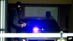 去年11月巴黎恐怖袭击事件的主要嫌疑人萨拉赫·阿卜德斯拉姆据信就在左边这位比利时警察身后的警车里。(2016年3月24日)