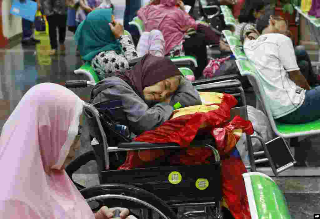 A patient takes a nap in her wheelchair as she waits with others at the registration desk at Dharmais Cancer Hospital in Jakarta, Indonesia. The hospital's information system was affected by the weekend's worldwide cyber attack.