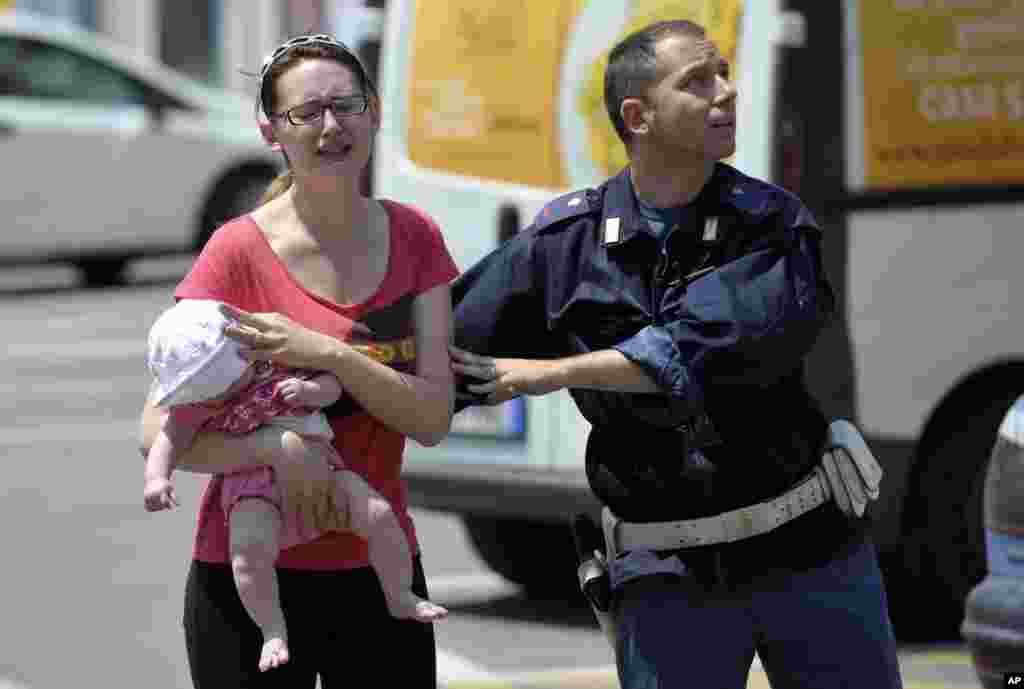Un policía italiano ayuda a una mujer que carga a su bebé durante el temblor y las réplicas que afectaron severamente la ciudad de Mirandola.