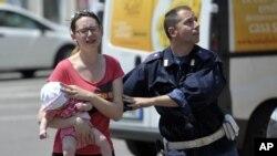Cảnh cảnh sát giúp đỡ phụ nữ và trẻ em tìm nơi trú ẩn ở Mirandola, miền Bắc nước Ý, ngày 29/5/2012