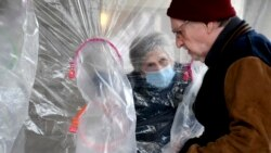 """Lynda Hartman is a 75 wife, visiting her 77-year-old husband, Len Hartman. They are using """"hug tent"""" set up outside the Juniper Village assisted living center in Louisville, Colorado, on Wednesday, Feb. 3, 2021. (AP Photo/Thomas Peipert)"""