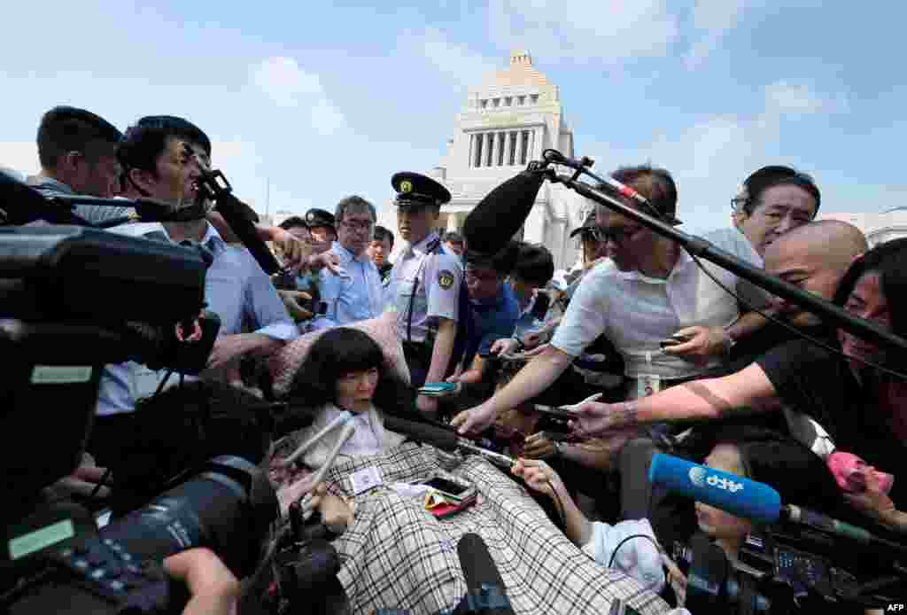 Japanese lawmaker Eiko Kimura (C) is surrounded by the media upon her arrival at Parliament in Tokyo. Two lawmakers with paralysis and who use wheelchairs are now representatives in Japan's upper house. It marks the first time people with severe disabilities have served in the body.