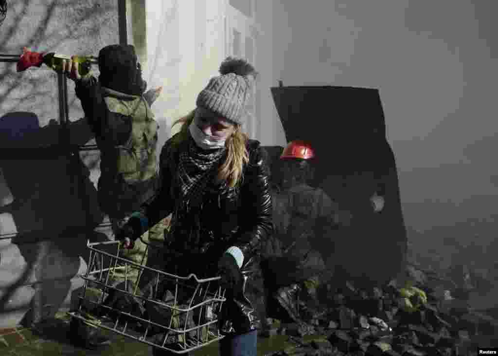 Seorang perempuan membawa batu dalam bentrokan antara demonstran anti-pemerintah dan para pegawai Kementerian Dalam Negeri di Kyiv (18/2).