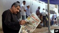 """Čovek ispred birališta čita lokalne novine na čijoj naslovnoj strani piše """"Egipat iznenadio svet"""",Kairo, 27. maj 2014."""