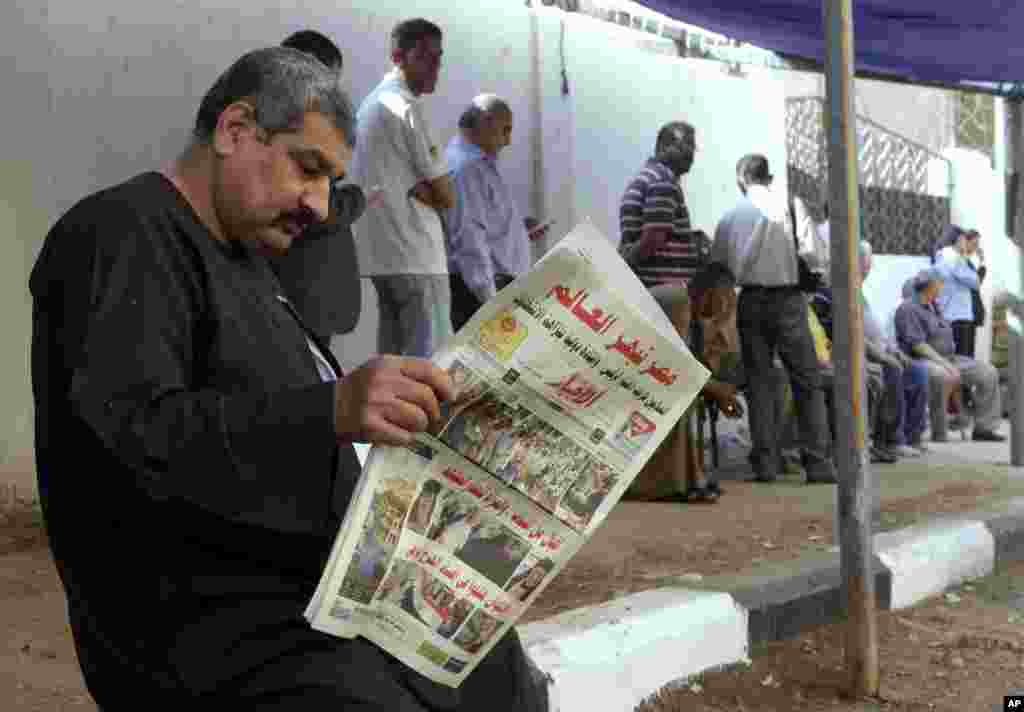 "A man reads a local newspaper with the headline in Arabic reading, ""Egypt surprises the world,"" outside a polling station in Cairo, May 27, 2014."