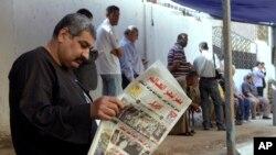 """Seorang pria membaca koran dengan judul berita utama """"Mesir Kejutkan Dunia"""", di luar sebuah TPS di Kairo (27/5). (AP/Amr Nabil)"""