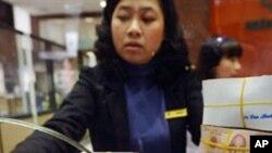 河内一家商业银行的工作人员从顾客手中接过成捆的钞票