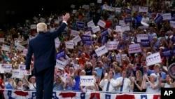共和党总统候选人川普在抵达位于卡罗来纳州威尔明顿的北卡罗来纳大学的竞选集会时向人群招手致意(2016年8月9日)