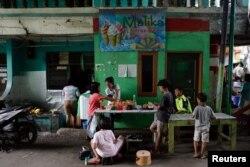 Anak-anak berkumpul di warung jajanan di lingkungan Muara Baru, di tengah pandemi COVID-19 di Jakarta, 14 Juli 2021. (REUTERS/Willy Kurniawan)