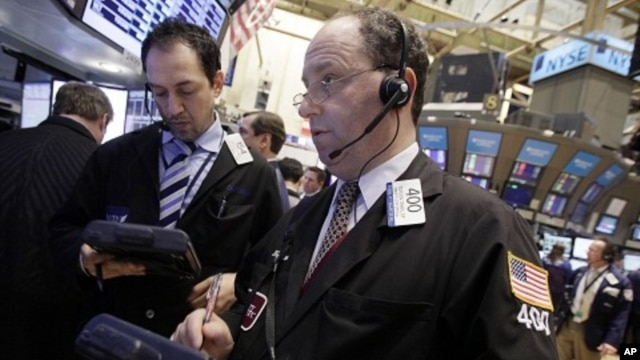 Gordon Charlop, right, works with fellow traders on the floor of the New York Stock Exchange. (March 2012 file photo)