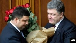 Ukraine's President Petro Poroshenko, right, and Volodymyr Groysman celebrate after Groysman was appointed prime minister during a parliament session in Kyiv, Ukraine, April 14, 2016, after lawmakers endorsed Arseniy Yatsenyuk's resignation.