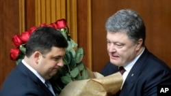 FILE - Ukraine's President Petro Poroshenko, right, and Volodymyr Groysman celebrate after Groysman was appointed prime minister during a parliament session in Kyiv, Ukraine, April 14, 2016, after lawmakers endorsed Arseniy Yatsenyuk's resignation.