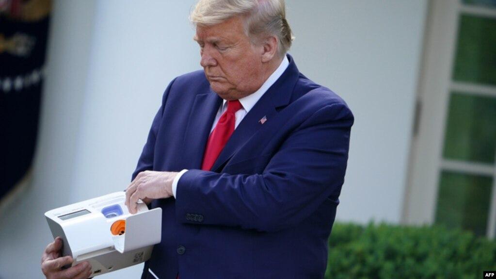 Tổng thống Donald Trump với bộ xét nghiệm Covid-19 của Abbott cho kết quả trong 5 phút.
