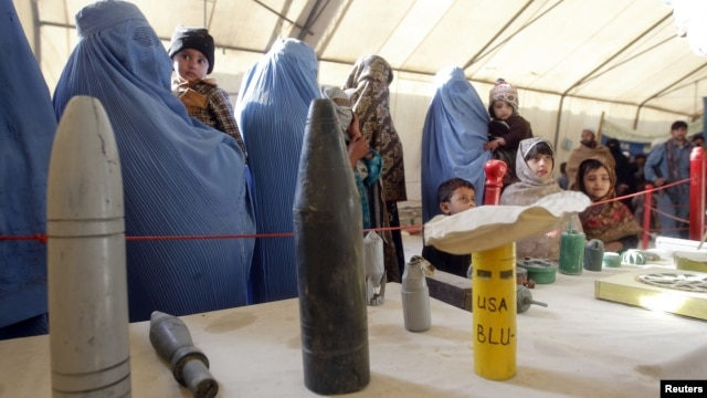 Afghan refugees family returning from Pakistan look at explosives and mines during an awareness program at the United Nations High Commissioner for Refugees registration center in Mommand Dara district in Jalalabad province, November 20, 2012.
