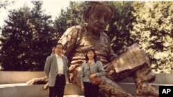 李淑娴和方励之1986年在华盛顿的美国科学院大门前的爱因斯坦雕像前合影。爱因斯坦手上的一张纸写有三个公式(从下到上):E=mc2;光电效应;广义相对论方程。注意:广义相对论方程中没有宇宙常数项