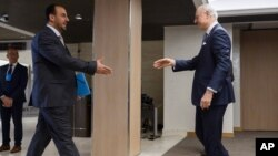 U.N. Special Envoy for Syria Staffan de Mistura, right, prepares to shake hands with Syria's main opposition High Negotiations Committee leader Nasr al-Hariri upon his arrival for a meeting during Syria peace talks in Geneva, Switzerland, Feb. 27, 2017.