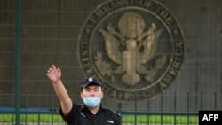 资料照片:美国驻北京大使馆外的一名中国保安在做手势。(2020年9月12日)