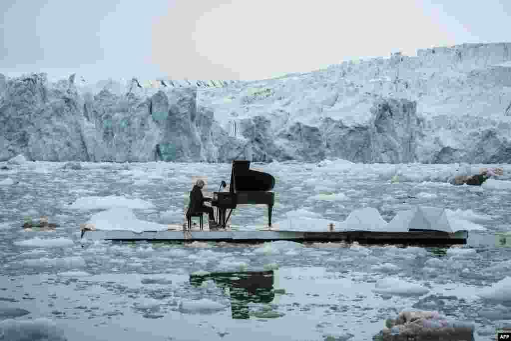 រូបភាពនេះបង្ហាញពី អ្នកនិពន្ធ និងអ្នកលេងព្យ៉ាណូ (pianist) ដែលមានឈ្មោះថា Ludovico Einaudi កំពុងដេញបទ Elegy for the Arctic នៅលើផ្ទាំងអណ្តែតមួយនៅក្នុងមហាសមុទ្រអាកទិច កាលពីថ្ងៃទី១៦ ខែមិថុនា ឆ្នាំ២០១៦ នៅពីមុខផ្ទាំងទឹកកក Wahlenbergbreen នៅប្រជុំកោះ Svalbard ក្បែរក្រុង Ny-Alesund ប្រទេសន័រវែស។