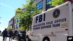 Mobil FBI, yang mengangkut tim untuk mengumpulkan bukti, diparkir di luar markas angkatan laut Washington (18/9). (AP/U.S. Navy)