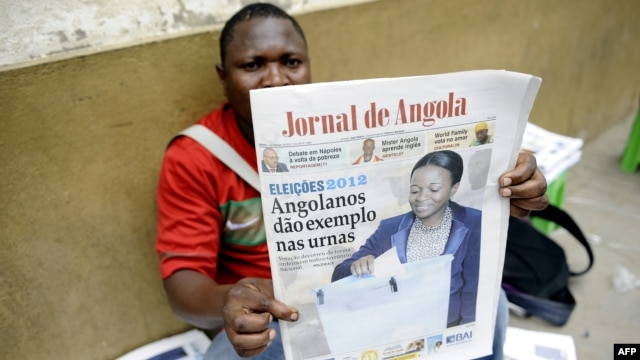 An Angolan newspaper street seller holds up a copy of the national paper in the street of Luanda, September 1, 2012.