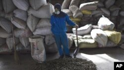 "A worker stands near the agricultural waste called ""green coal"" fuel pellets on the floor inside a factory outside of Beijing, China. (File 2009)"