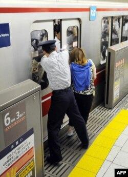 Seorang petugas membantu penumpang yang tasnya terjepit pintu kereta sementara sebuah KRL bersiap berangkat dari Stasiun Ikebukuro di Tokyo, Jepang, 12 Juli 2013.