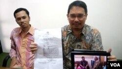 Ketua Tim Pembela Kemanusiaan, Trisno Raharjo (kanan) menunjukkan surat pemanggilan polisi kepada Mardiyo, ayah almarhum Siyono dan foto di kantor Polisi. Sebelah kiri Eko Riyadi dari Pusat Studi Hukum dan HAM - UII.