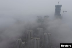 FILE - Buildings are seen shrouded in heavy haze at Qingdao development zone, Shandong province, Feb. 25, 2014.