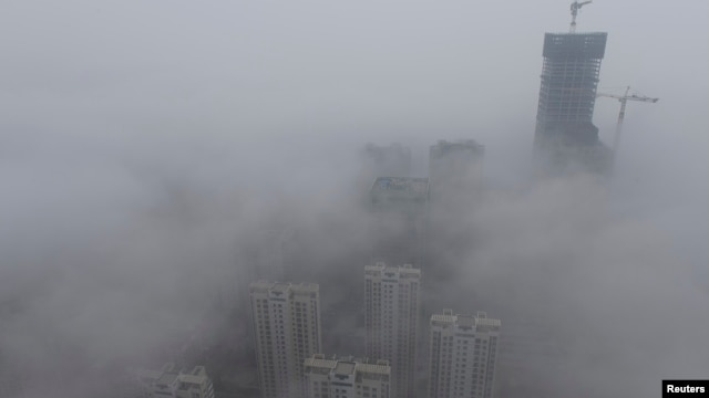 FILE -- Buildings are seen shrouded in heavy haze at Qingdao development zone, Shandong province.