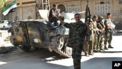 Binh sĩ Syria làm dấu hiệu chiến thắng sau khi đào thoát với các đồng đội để gia nhập phe nổi dậy tại khu phố Khaldiyeh trong tỉnh Homs