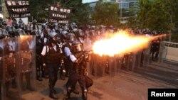 一名香港警察在《逃犯條例》抗議遊行中,使用催淚瓦斯。 (2019年6月12日)