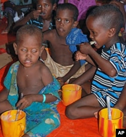 Newly arrived Somali refugee children receive their first hot meal of cereal at a feeding center run by Save the Children USA at the Dollo Ado refugee reception station, Ethiopia, October 26, 2011