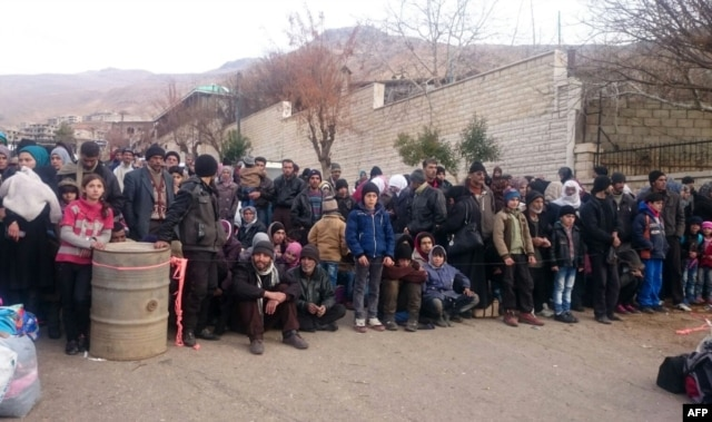 FILE - Syrians wait for the arrival of an aid convoy in the besieged town of Madaya, Jan. 11, 2016.