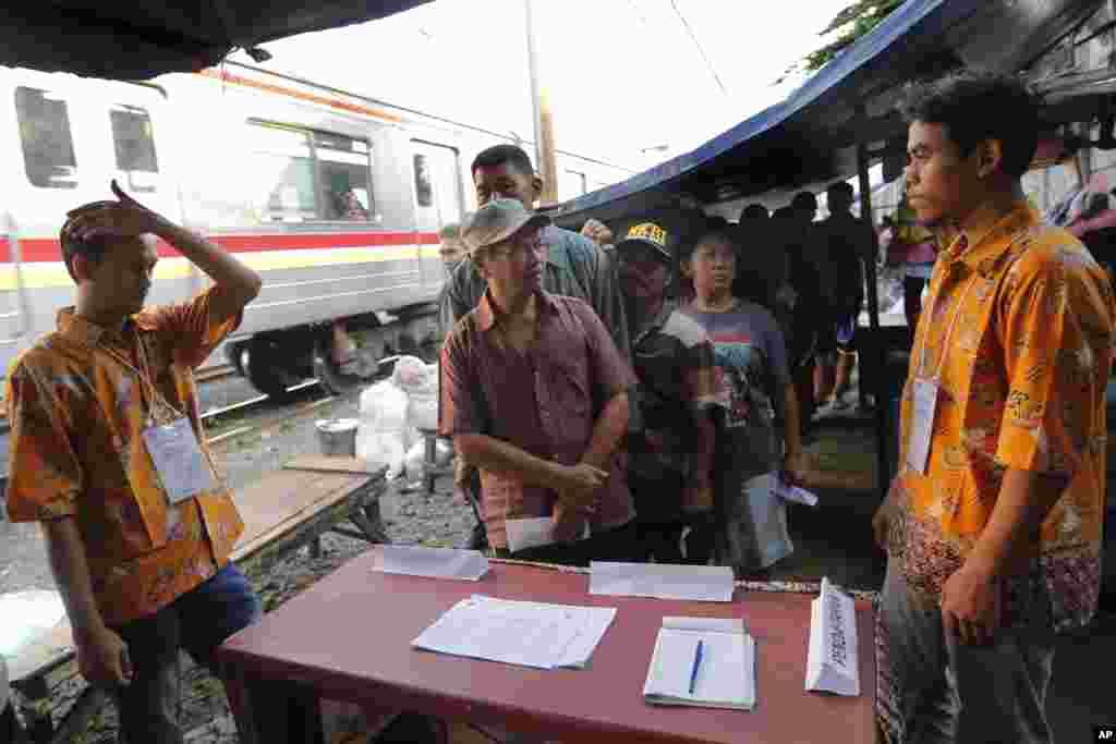 Warga antre untuk melaksanakan hak pilih di sebuah TPS yang didirikan di sebelah jalur kereta api di Jakarta, Rabu (17 April 2019). (Foto: Tatan Syuflana/AP)