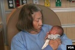신생아집중치료실 자원봉사자인 캐롤린 키하노 씨가 아기를 품에 앉아주고 있다.