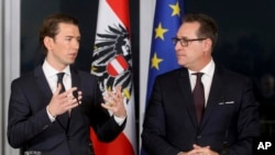Leader of the Austrian People's Party, OVP, Sebastian Kurz and Heinz-Christian Strache, chairman of the right-wing Freedom Party, FPO, from left, talk during a joint news conference after forming a new coalition government in Vienna, Austria, Dec. 16, 2017.