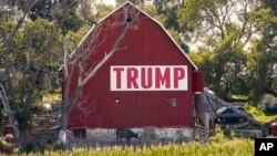 FILE - Corn grows in front of a barn displaying a large Trump sign in rural Ashland, Nebraska, July 24, 2018.