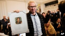 Cartoonist Lars Vilks holds the Danish Free Press Society's Sappho Prize, which he received for his efforts on behalf of freedom of speech at an meeting in the Danish Parliament at Christiansborg Castle, Copenhagen, March 14, 2015.