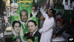 Pakistani vendors fix posters of candidates taking part in the upcoming parliamentary elections in Lahore, Pakistan, April 5, 2013.