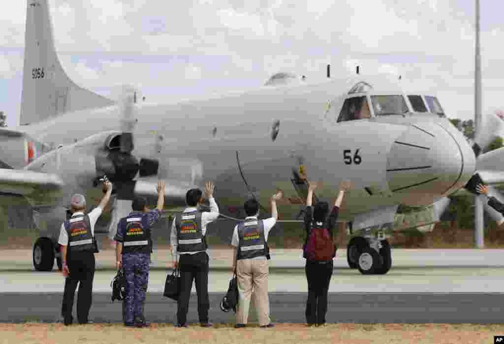 Members of Japan's disaster relief team wave to a Japan Maritime Self-Defense Force aircraft as it prepares to to search for flight MH370, at the Royal Australian Air Force Base Pearce in Perth, March 24, 2014.
